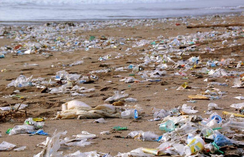 praia poluída com plásticos descartáveis
